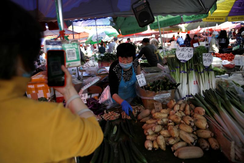 A customer scans a WeChat QR code to pay at amarket in Beijing, April2020