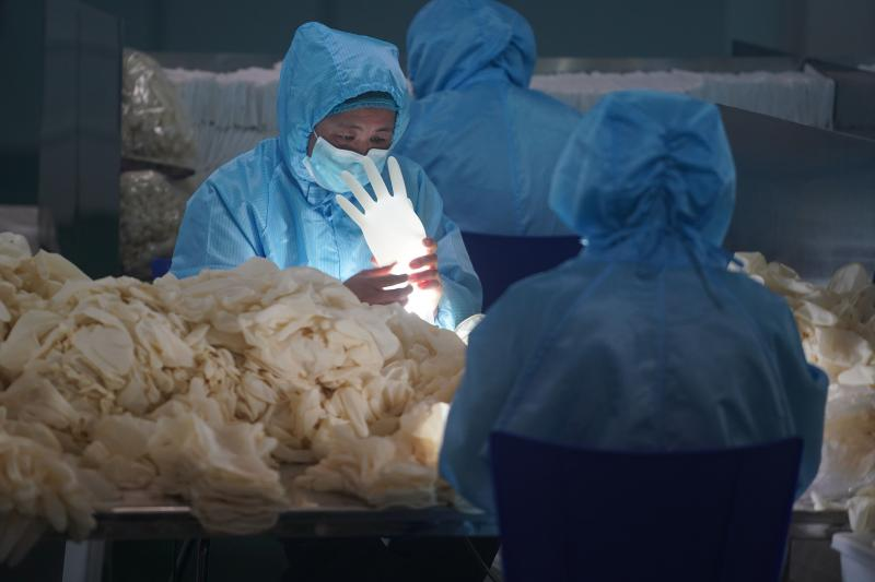 Workers check sterile medical gloves in Nanjing, China, February 2020