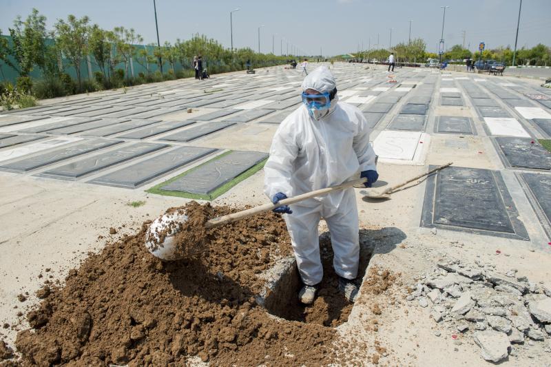 A gravedigger buries a victim of the new coronavirus inTehran, Iran, April 2020