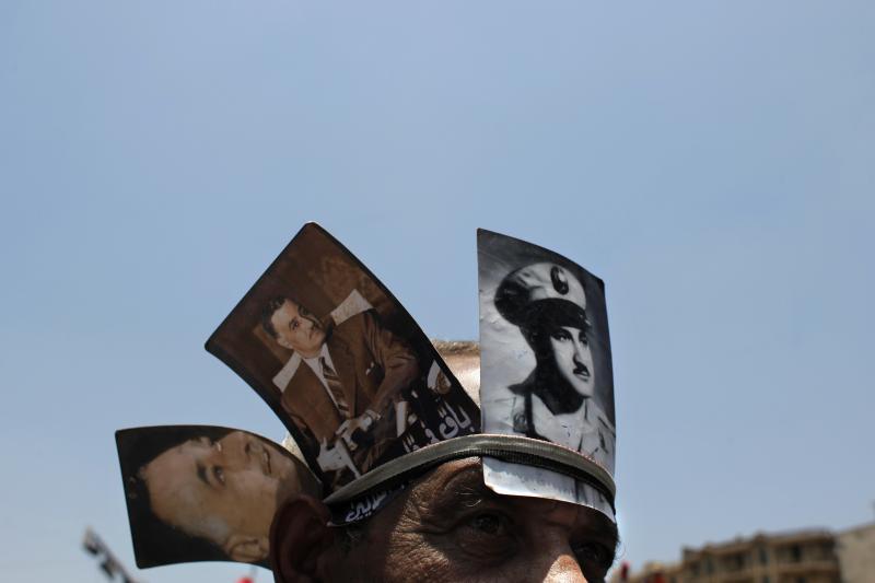 An Egyptian protester, wearing pictures of late Egyptian President Gamal Abdel Nasser on his head, attends a demonstration at Tahrir Square, Cairo, Egypt on Friday, June 8, 2012