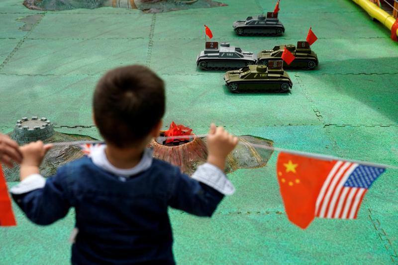 A boy looking at remote control tank toysin Shanghai, China, May2019