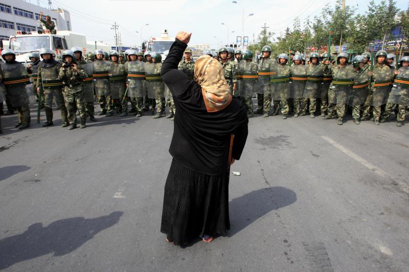 A womanshouts at Chinese paramilitary police in Urumqi, China,July 2009