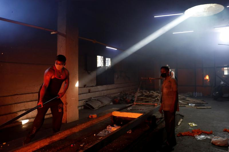 Municipal workers at a crematorium in New Delhi, India, May 2021