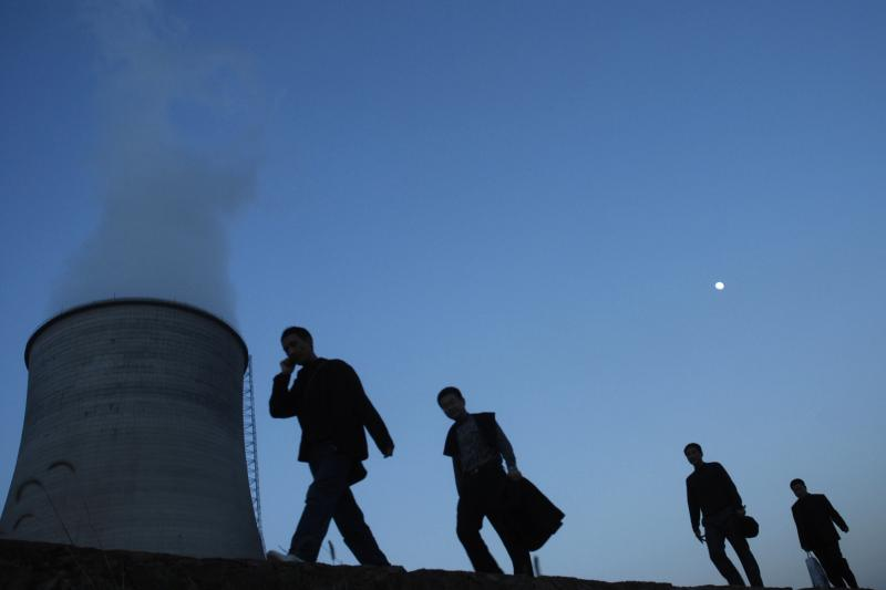 People walking by a cooling tower in Yingtan, Jiangxi Province, China, December 11, 2008