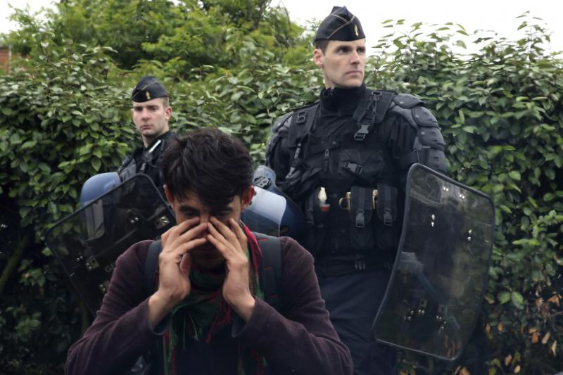 An Afghan immigrant wipes his eyes as police evacuate him and others at an improvised camp in Calais, northern France, May 28, 2014.