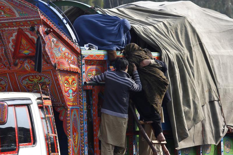 An elderly Afghan refugee woman is helped by family members to board a truck as they prepare to go back to Afghanistan. Afghan immigrants have been ordered out of Pakistan in what officials say is a bid to root out militants, Peshawar February 18, 2015.