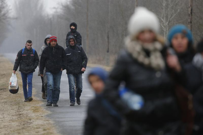 A group of Kosovars walk along a road after they crossed the Hungarian-Serbian border near the village of Asotthalom February 6, 2015.