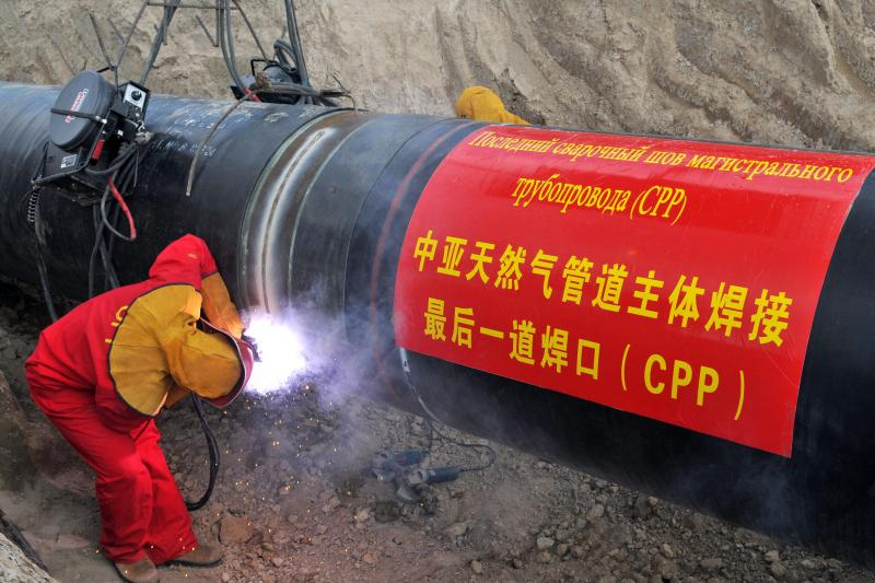 """Workers complete welding of the last pipe links of Kazakhstan's segment of a pan-Central Asian gas pipeline. The sign on the pipe reads in Russian """"The last welding connection of trunk gas pipeline."""""""