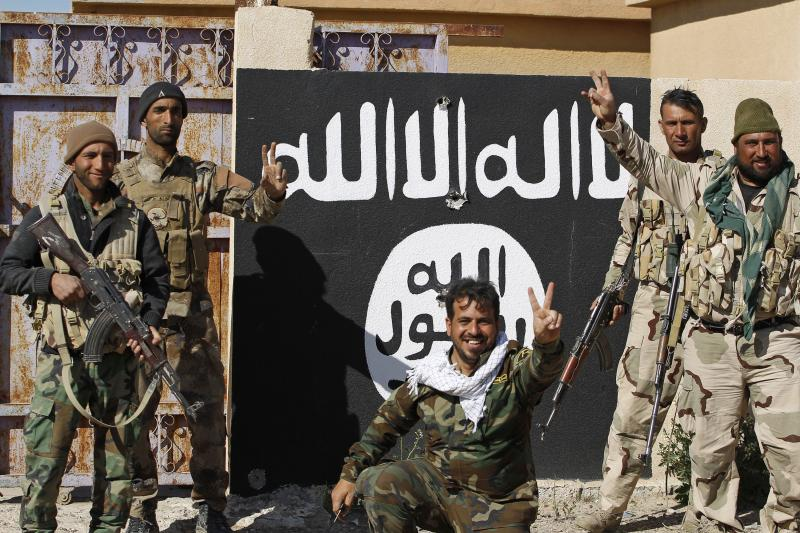 Shia fighters stands near a wall painted with the black flag commonly used by Islamic State militants in the town of Tal Ksaiba, near the town of al-Alam, March 7, 2015.