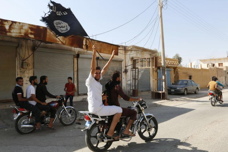 A resident of Tabqa waves an ISIS flag in celebration after Islamic State militants took over Tabqa air base, in nearby Raqqa city, August 24, 2014.