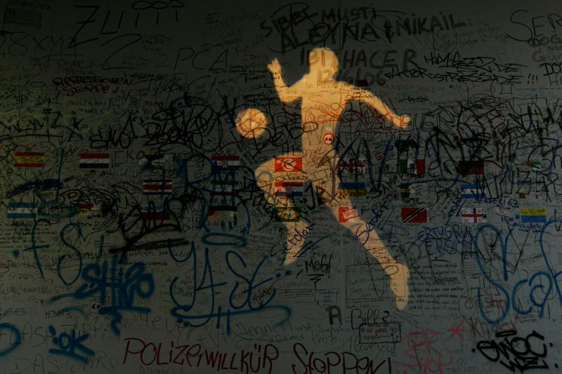 A picture of a soccer player is projected on a wall with graffiti and greetings by soccer fans in Dortmund, June 13, 2006.