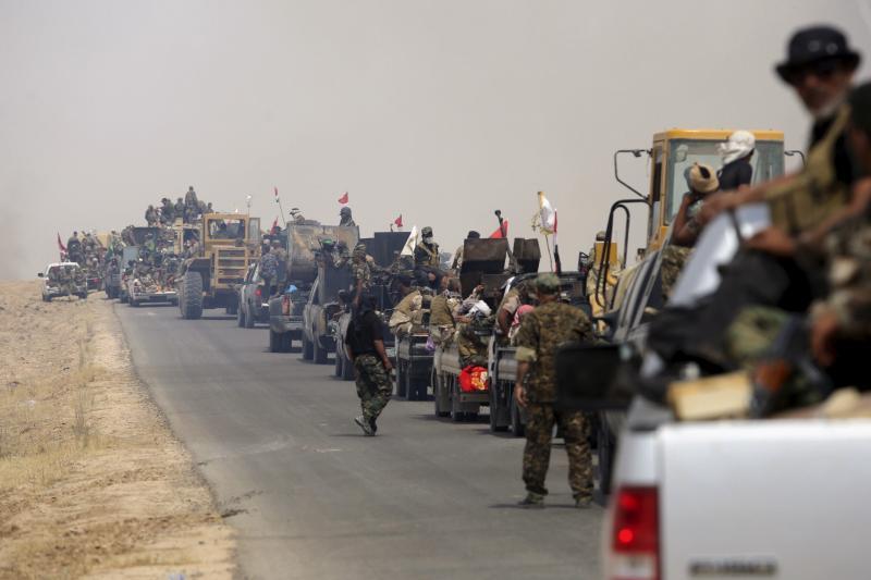Shia paramilitaries riding military vehicles travel from Lake Tharthar toward Ramadi to fight against Islamic state militants, west of Samarra, Iraq May 27, 2015.