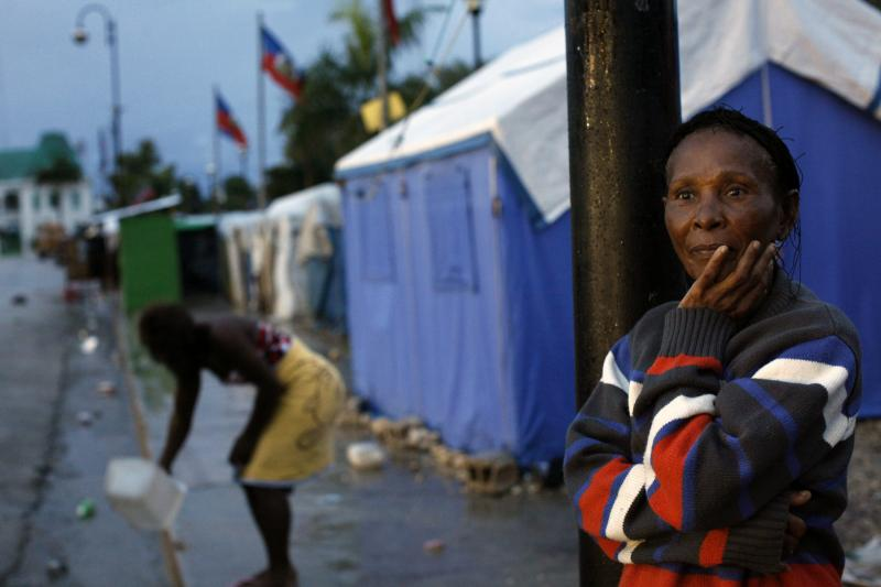 An earthquake survivor looks at the rain in the early morning in a provisional camp in downtown Port-au-Prince, November 5, 2010.