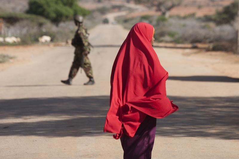 A woman walks by on the outer perimeter area of the Kismayu airport controlled by the African Mission in Somalia (AMISOM), November 11, 2013.