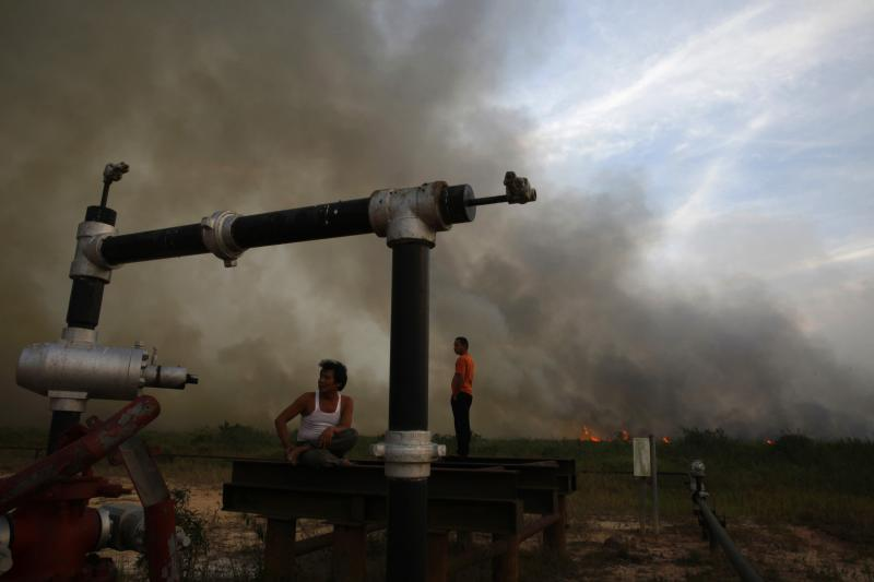 Villagers rest on an oil well as a fire burns a palm oil plantation at the haze hit Bangko Pusako district in Rokan Hilir, in Indonesia's Riau province, June 22, 2013.