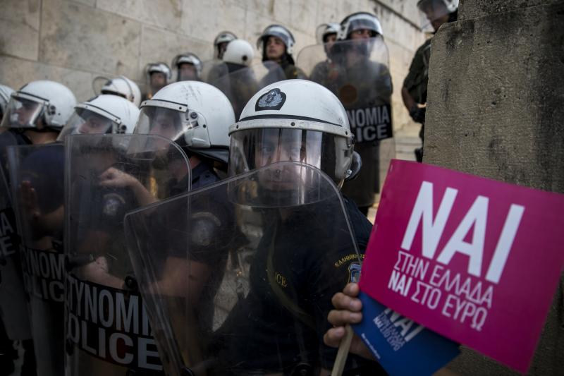 Riot policemen stand guard next to a small flag with the word 'Yes' in Greek during a rally in front of the parliament building, in Athens, Greece, June 30, 2015.