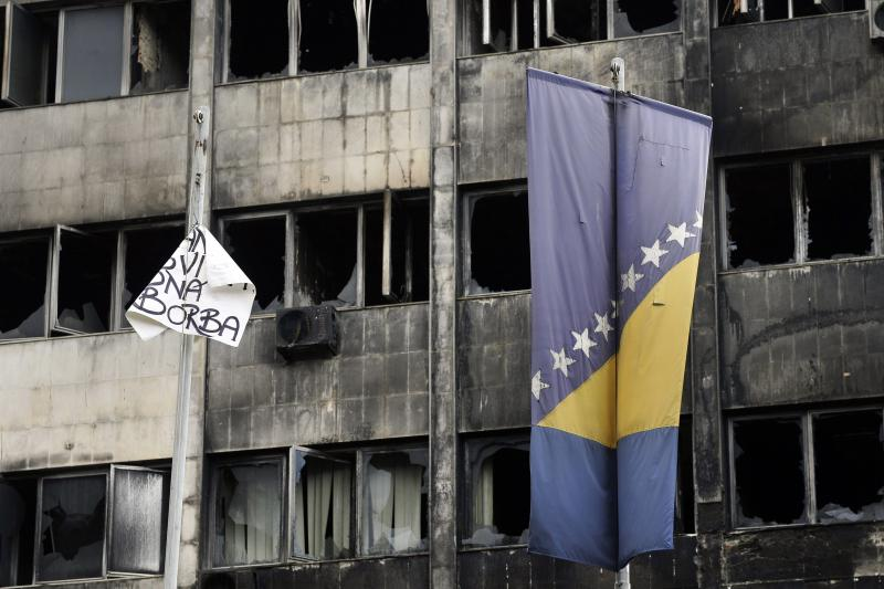 A Bosnian flag and a sign flutter in front of a burned government building in Tuzla, February 8, 2014. Protesters across Bosnia set fire to government buildings and fought with riot police on Friday as long-simmering anger over lack of jobs and political