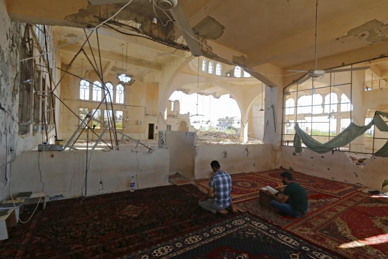 Men pray inside a damaged mosque during the  month of Ramadan in Qmenas village, in Idlib province, June 30, 2015.