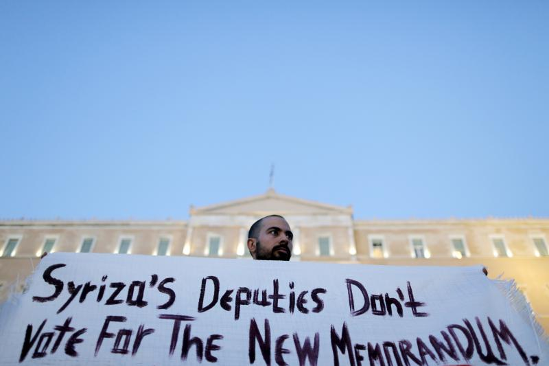 An anti-EU protester holds a banner in front of the parliament building during a demonstration of about five hundred people in Athens, July 13, 2015.