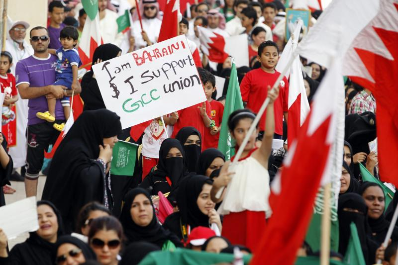 A pro-government protester holds up a placard as she participates in a rally to show support towards GCC Union, in al Fateh Grand Mosque in Manama, May 19, 2012.