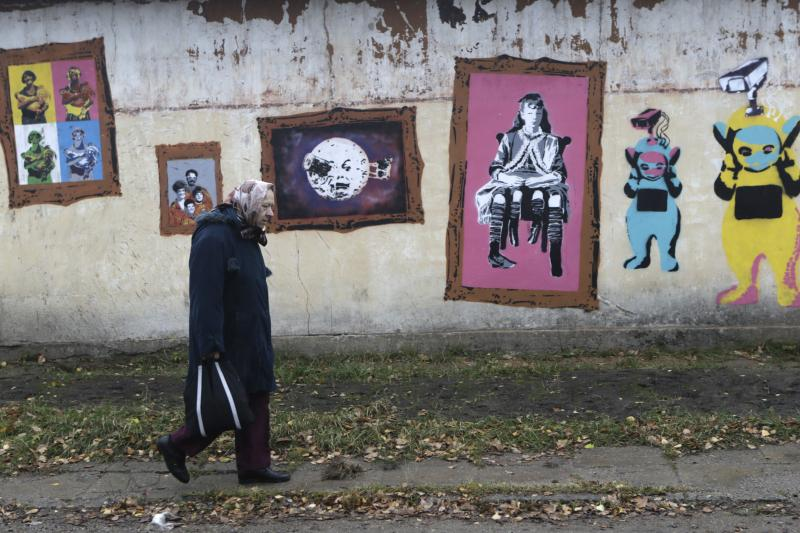 A woman walks past a wall with graffiti in Valka, October 26, 2013.