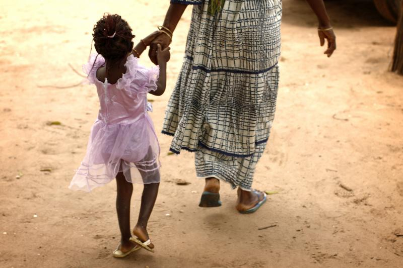 A mother and daughter walk home after a meeting of women from several communities who are working to eradicate female genital mutilation, in the western Senegalese village of Diabougom September 10, 2007.