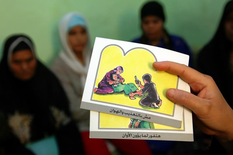 A counsellor holds up cards used to educate women about female genital mutilation in Minia, Egypt, June 13, 2006.