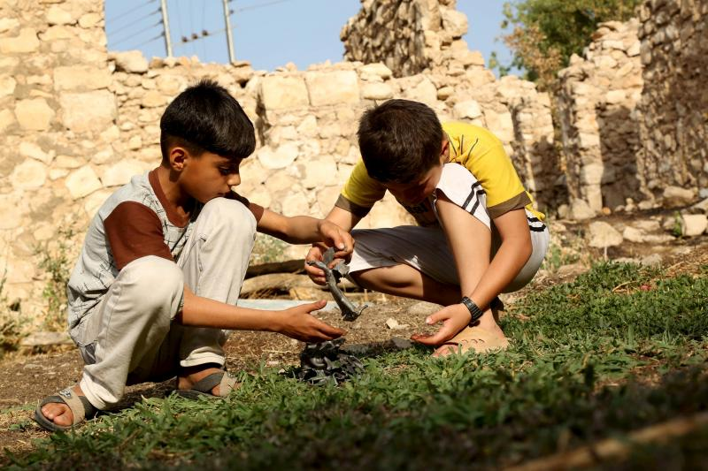 Boys hold pieces of metals from a crater crater caused by a Turkish air strike against Kurdistan Workers Party (PKK) camps in the village of Amadiya, outskirts of Dohuk province July 29, 2015.