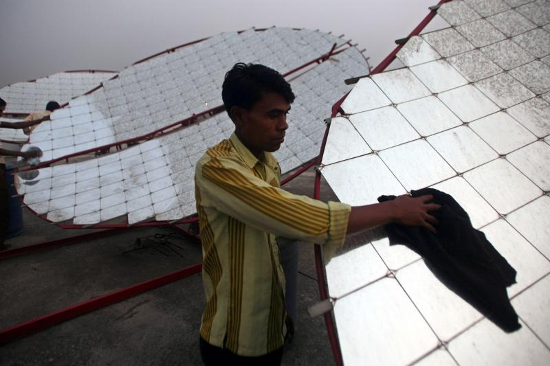 Workers clean solar concentrator panels at the Tapi solar food processing unit at Kapodra village, about 220 miles south of the Indian city of Ahmedabad, December 16, 2009.