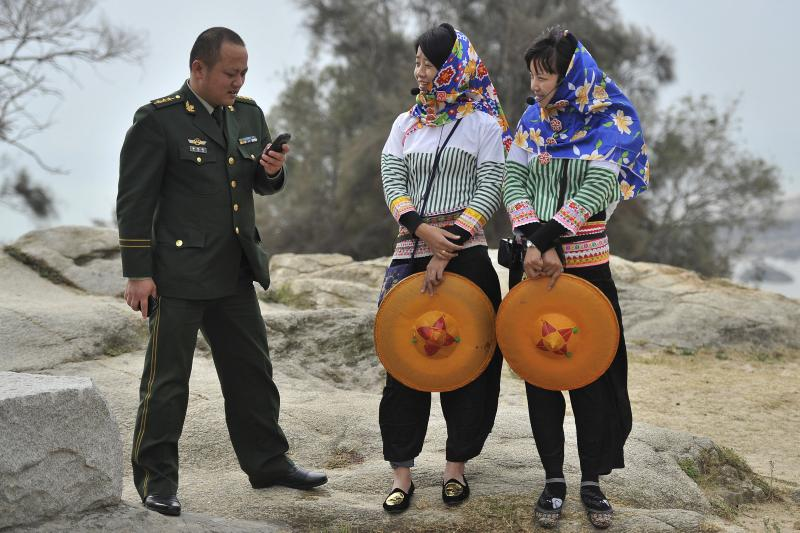 A People's Liberation Army officer looks at his mobile phone as he speaks with two Hui'an maiden tourist guides in Hui'an county, December 8, 2013.