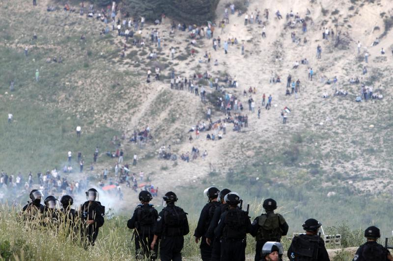 Israeli security forces stand in their position in the Druze village of Majdal Shams in the Golan Heights, as protesters are seen on the Syrian side of the Israeli-Syrian border, June 5, 2011.