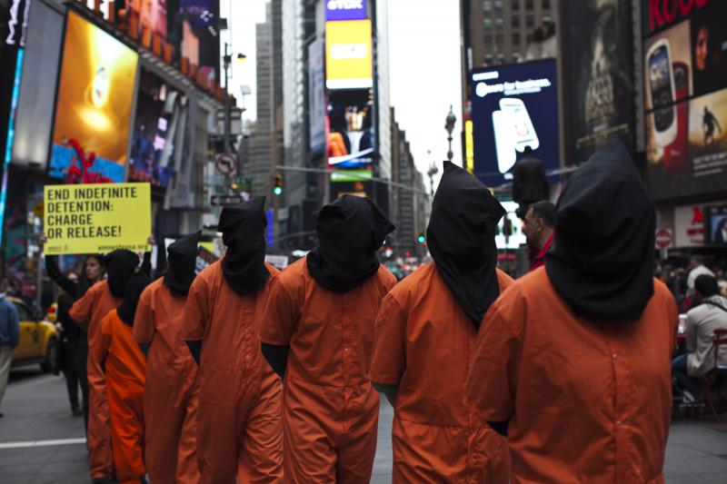 Activists dressed as prisoners demand the closure of the U.S. military's detention facility in Guantanamo Bay, Cuba while taking part in a protest in Times Square, New York, April 2013.