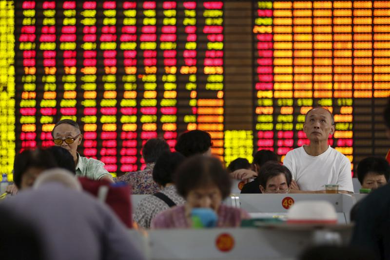 Investors look at computer screens showing stock information at a brokerage in Shanghai, August 13, 2015.