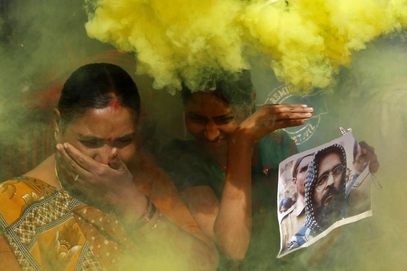 Demonstrators hold a poster of Mohammad Afzal Guru, a Kashmiri militant that India hanged for an attack on the country's parliament in 2001, as they take cover from coloured smoke released by fellow demonstrators, February 9, 2013.