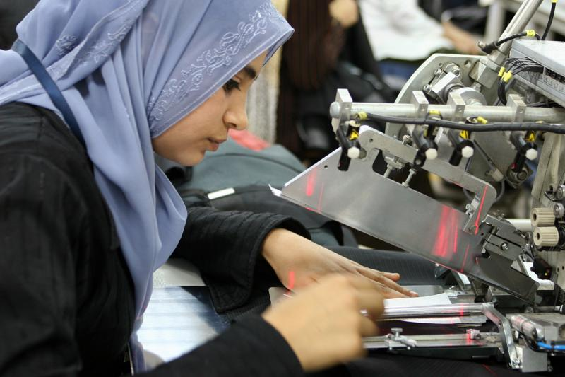 A seamstress cuts fabric with a laser cutting machine in a factory that makes and exports Valentino men's suits in 10th of Ramadan City, Egypt February 22, 2006. This factory, like many others, is in a Qualified Industrial Zone (QIZ)