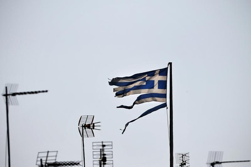 A frayed Greek national flag flutters among antennas atop a building in central Athens, Greece July 20, 2015.
