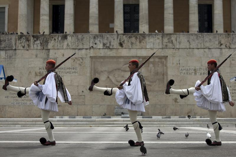 Greek Presidential guards take part in a ceremonial change of guards at the Monument of the Unknown Soldier in front of the Parliament building in Athens, Greece, August 23, 2015.