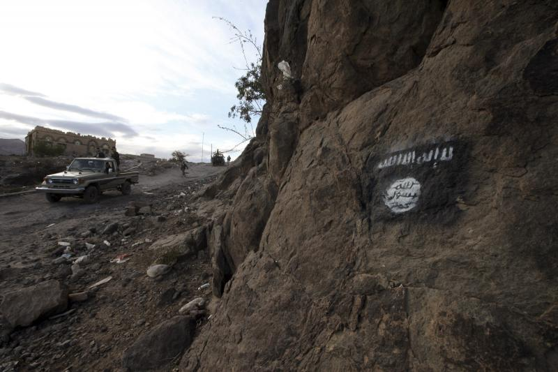 Houthi rebels drive a patrol truck past a Ansar al-Sharia flag painted on the side of a hill in Rada, November 22, 2014.  Ansar al-Sharia is the local wing of Al Qaeda in the Arabian Peninsula (AQAP).