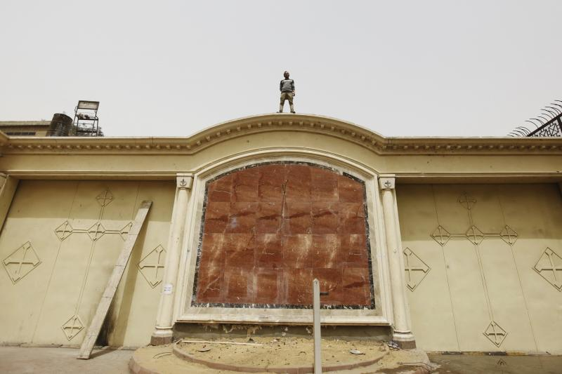 A Coptic Christian man stands on the wall of Cairo's main Coptic cathedral April 8, 2013.