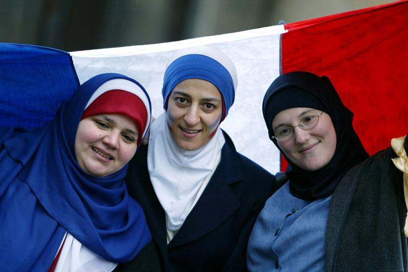 Young muslim girls demonstrate with a French flag in favor of the Islamic headscarf