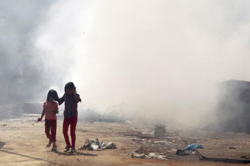 Girls walk near garbage on fire, piled up along a street in the Chiah area in Beirut, Lebanon August 27, 2015.