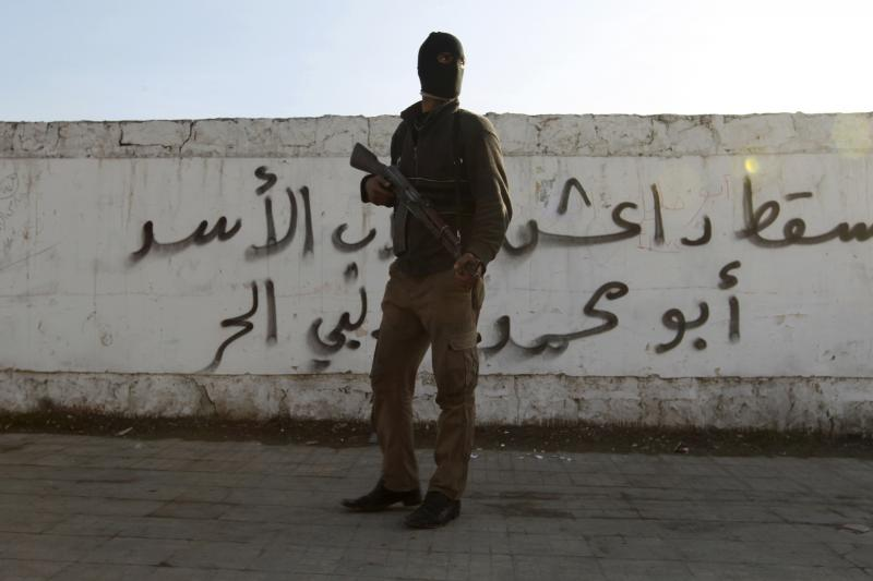 """A Free Syrian Army fighter carries his weapon as he stands in front of graffiti that reads """"Daesh (Islamic State of Iraq and the Levant ) down"""" at Masaken Hanano neighborhood in Aleppo January 7, 2014."""