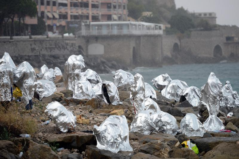 A group of migrants protect themselves from the weather with emergency blankets as they huddle on the seawall at the Saint Ludovic border crossing on the Mediterranean Sea between Vintimille, Italy and Menton, France, June 14, 2015.