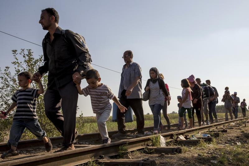 Migrants walk along a railway track outside the village of Horgos in Serbia toward the border it shares with Hungary, September 2, 2015.