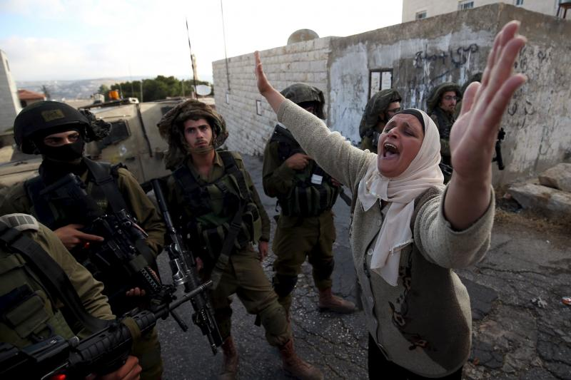 A Palestinian woman confronts Israeli soldiers