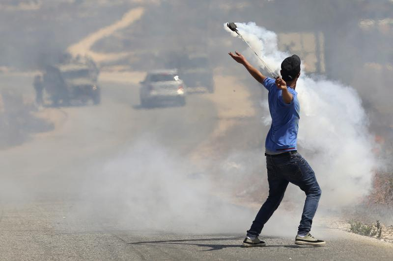 Palestinian protester uses slingshot to return tear gas canister