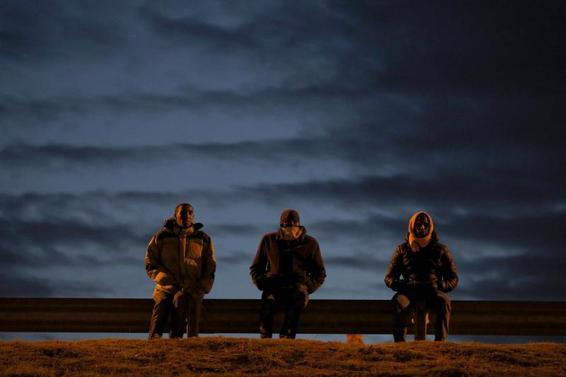 Migrants sit by a roadside as darkness falls, near to the Eurotunnel site in Calais, France, August 4, 2015.