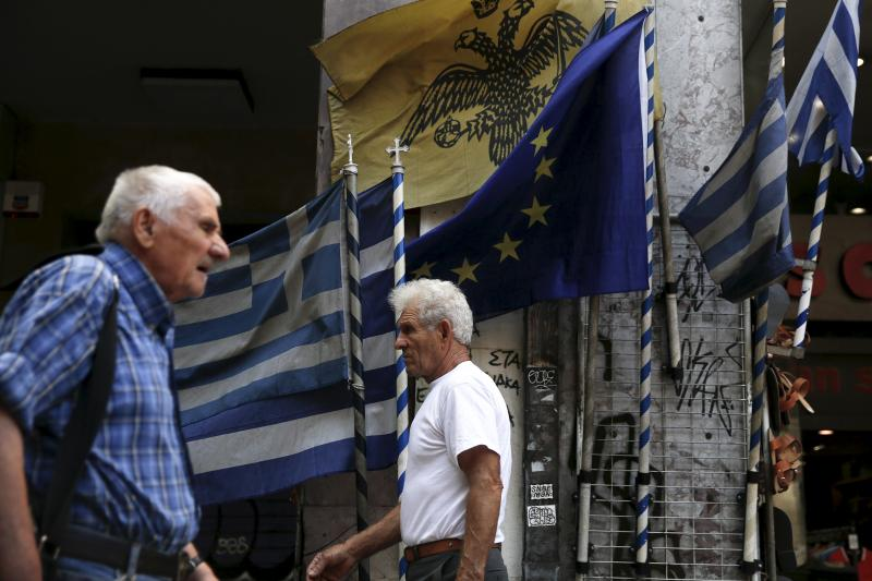 People walk next to Greek national flags and a European Union flag in Athens, August 27, 2015.