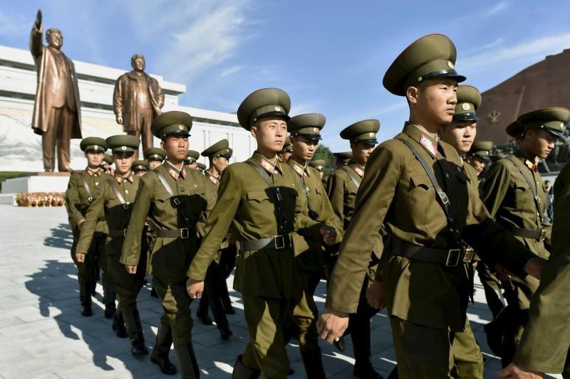 North Korean soldiers walk in front of bronze statues of North Korea's late founder Kim Il Sung and late leader Kim Jong Il as they visit at Mansudae in Pyongyang, September 9, 2015.