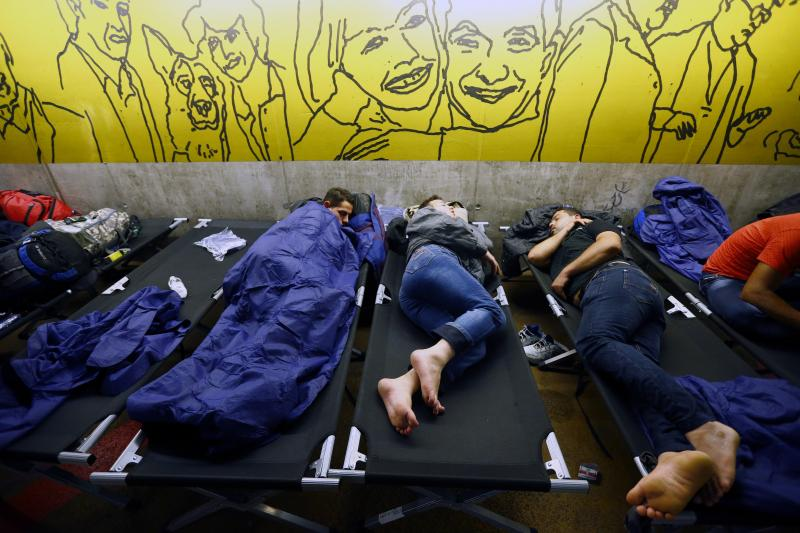 Migrants rest inside an improvised shelter in the underground parking of a train station in Salzburg, Austria September 13, 2015.